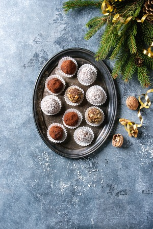 Variety of homemade dark chocolate truffles with cocoa powder, coconut, walnuts as Christmas gift on vintage tray with fir tree, Christmas decorations above over blue background. Top view, space. Stock Photo