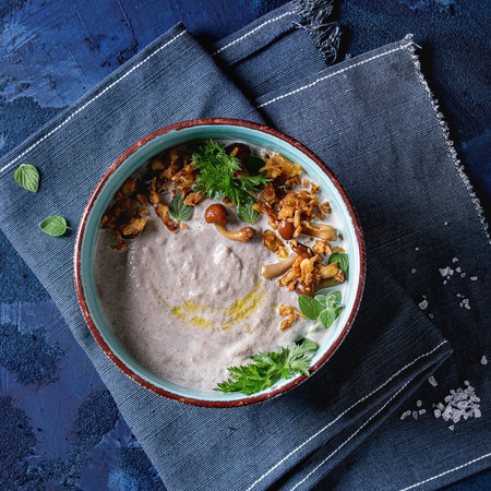 Mushroom cream soup in ceramic bowl served with forest mushrooms, greens, fried onion on blue textile napkin over dark blue texture concrete background. Top view with space. Square image