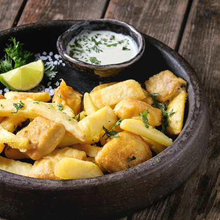 Traditional british fast food fish and chips. Served with white cheese sauce, lime, parsley in terracotta tray over old wooden plank background. Close up. Square image