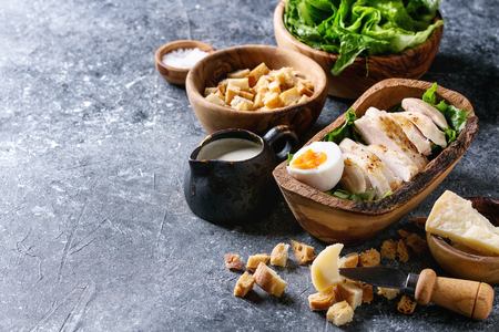 Bowls of ingredients for cooking classic Caesar salad. Sliced baked chicken breast, green roman salad, parmesan cheese, egg, croutons, salt, jug of sauce over dark gray texture background. Copy space.