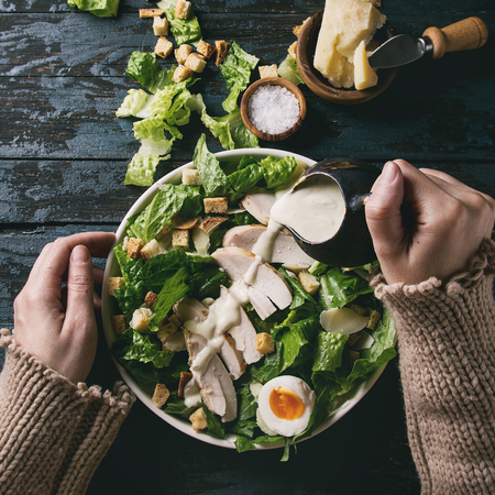 Female hands powring dressing to Classic Caesar salad with chicken breast in white ceramic plate. Served with ingredients above over old dark blue wooden background. Flat lay. Rustic style