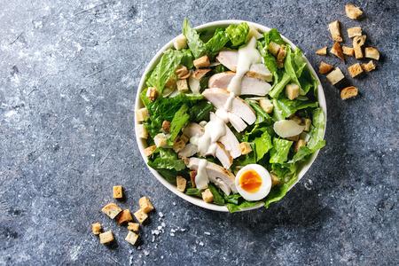 Salada Caesar clássica com peito de frango grelhado e metade do ovo em placa de cerâmica branca. Servido com croutons e vestir-se sobre o fundo cinzento escuro da textura. Vista de cima, espaço. Foto de archivo