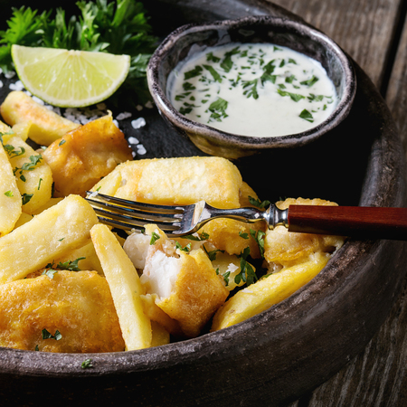 Traditional british fast food fish and chips. Served with white cheese sauce, lime, parsley, fork in terracotta tray over old wooden plank background. Close up. Square image Reklamní fotografie