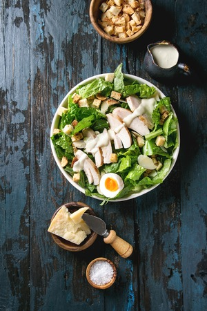 Classic Caesar salad with grilled chicken breast and half of egg in white ceramic plate. Served with ingredients above over old dark blue wooden background. Top view, space.