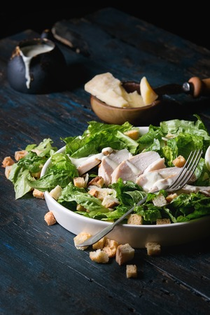 Classic Caesar salad with grilled chicken breast and half of egg in white ceramic plate. Served with fork and ingredients above over old dark blue wooden background. Rustic style