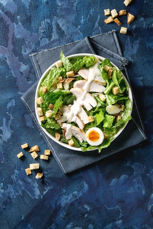 Classic Caesar salad with grilled chicken breast and half of egg in white ceramic plate. Served with croutons and dressing on textile napkin over dark blue texture background. Top view, space.