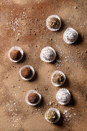 Variety of homemade dark chocolate truffles with cocoa powder, coconut, walnuts over cocoa powder as background. Top view, copy space. Stok Fotoğraf