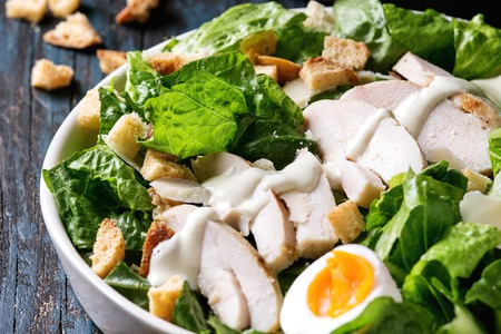 Classic Caesar salad with grilled chicken breast and half of egg in white ceramic plate. Over old dark blue wooden background. Close up. Rustic style Stock Photo