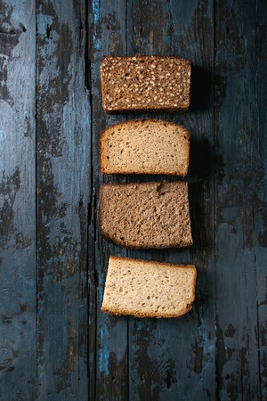 Variety loaves of sliced homemade rye bread whole grain and seeds over old dark wooden background. Top view, space. Healthy eating Imagens