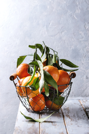 Ripe organic clementines or tangerines with leaves in basket standing on white wooden plank table with gray wall as background. Rustic style. Healthy eating