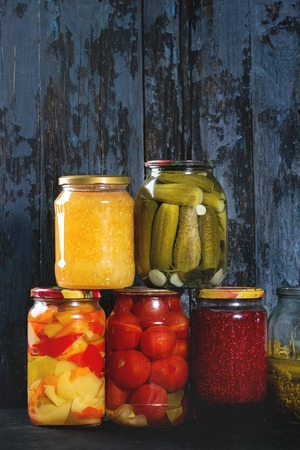 Variety glass jars of homemade pickled or fermented vegetables and jams in row with old dark blue wooden plank background. Seasonal preserves. Banco de Imagens