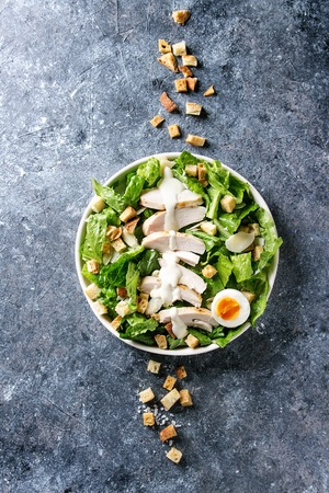 Classic Caesar salad with grilled chicken breast and half of egg in white ceramic plate. Served with croutons and dressing over dark gray texture background. Top view, space.