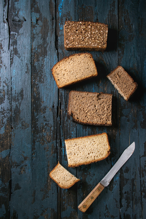 Variety loaves of sliced homemade rye bread whole grain and seeds with knife over old dark wooden background. Top view, space. Healthy eating