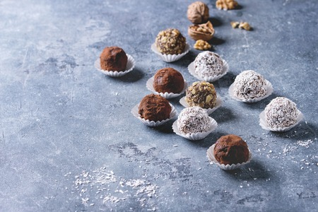 Variety of homemade dark chocolate truffles with cocoa powder, coconut, walnuts over blue texture background. Copy space.