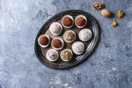 Variety of homemade dark chocolate truffles with cocoa powder, coconut, walnuts on vintage tray over blue texture background. Top view, copy space. Stock Photo