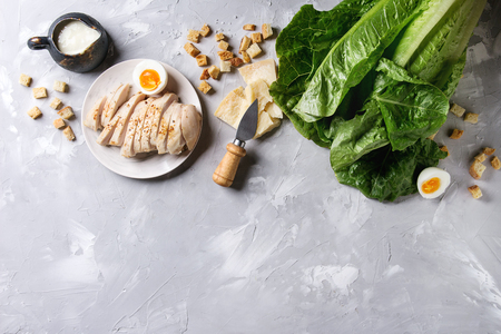 Ingredients for cooking classic Caesar salad. Sliced baked chicken breast, green roman salad, parmesan cheese, boiled egg, croutons, salt, jug of sauce over gray texture background. Top view, space. Stock Photo