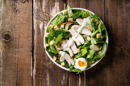 Classic Caesar salad with grilled chicken breast and half of egg in white ceramic plate. Served with croutons and dressing over old wooden background. Top view, space. Stock Photo