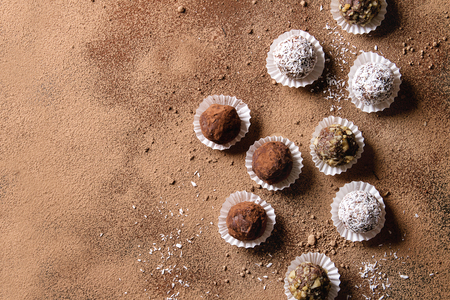 Variety of homemade dark chocolate truffles with cocoa powder, coconut, walnuts over cocoa powder as background. Top view, copy space. Stock Photo