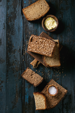 Variety loaves of sliced homemade rye bread whole grain and seeds for breakfast with olive wood bowls of butter and salt over old dark wooden background. Top view, space. Imagens