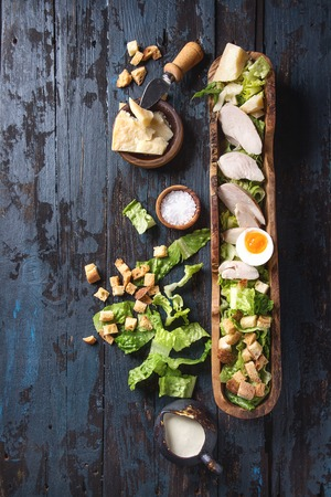 Classic Caesar salad with grilled chicken breast and half of egg in olive wood bowl. Served with ingredients above over old dark blue wooden background. Top view, space. Rustic style