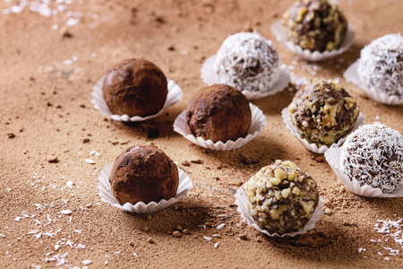 Variety of homemade dark chocolate truffles with cocoa powder, coconut, walnuts over cocoa powder as background. Close up, copy space.