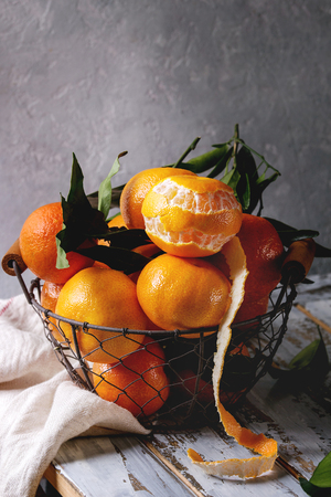 Ripe organic clementines or tangerines with leaves in basket standing with kitchen towel on white wooden plank table with gray wall as background. Rustic style. Healthy eating