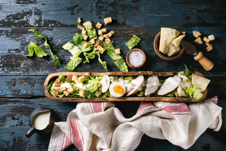 Classic Caesar salad with grilled chicken breast and half of egg in olive wood bowl. Served on kitchen towel with ingredients above over old dark blue wooden background. Top view, space. Rustic style