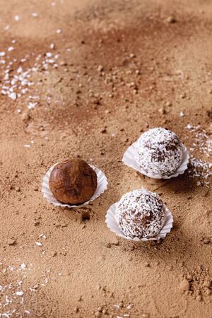Variety of homemade dark chocolate truffles with cocoa powder, coconut, walnuts over cocoa powder as background. Copy space. Stock Photo