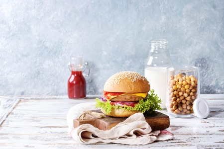 Homemade burger in classic bun with tomato sauce, lettuce, meat, cheese, onion on wood serving board owith bottle of ketchup, milk, roast chickpeas ver white wooden plank table. Homemade fast food.