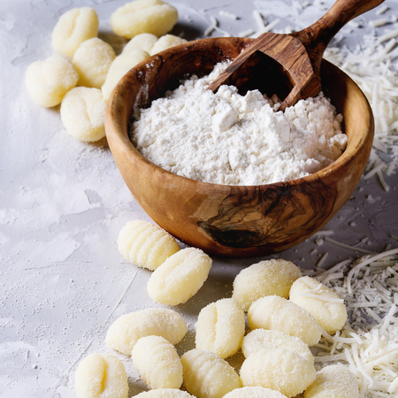 Raw uncooked potato gnocchi with olive wood bowl of flour, grated parmesan cheese over gray concrete background. Close up with copy space. Home cooking. Square image