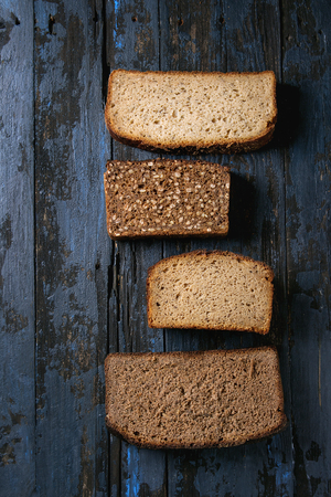 Variety loaves of sliced homemade rye bread whole grain and seeds over old dark wooden background. Top view, space. Healthy eating Banco de Imagens