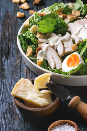 Classic Caesar salad with grilled chicken breast and half of egg in white ceramic plate. Served with ingredients above over old dark blue wooden background. Close up. Rustic style