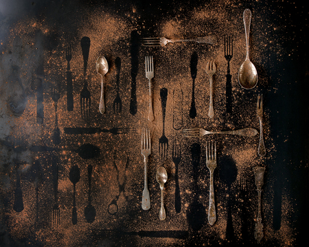 Big set of vintage and disappeared cutlery under brown dust over black metal background. Top view