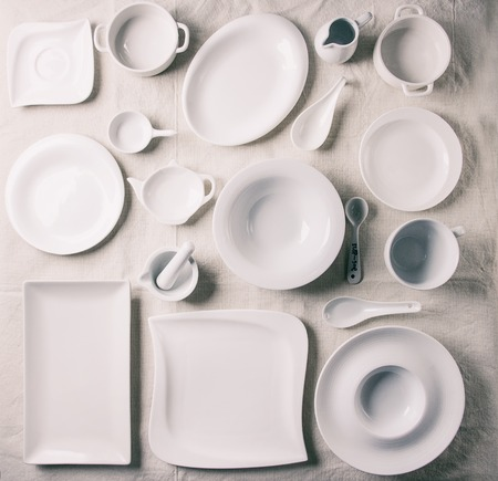 Big set of empty white porcelain plates and other tableware different size and shapes over white linen tablecloth. Flat lay