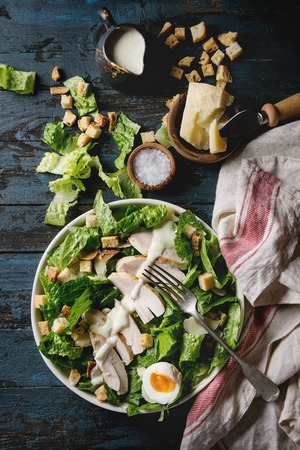 Classic Caesar salad with grilled chicken breast and half of egg in white ceramic plate. Served on towel with ingredients above over old dark blue wooden background. Top view, space. Rustic style Stock Photo