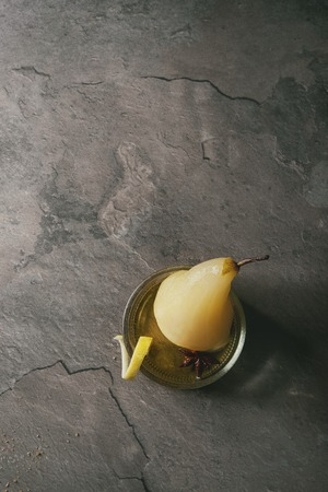 Traditional dessert poached pear in white wine served in glass bowl with syrup and lemon zest over gray texture table. Top view with space Stock Photo - 90953002