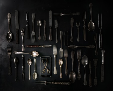 Big set of vintage cutlery with smartphote over black metal background. Top view