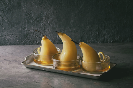 Traditional dessert poached pears in white wine served in glass bowls with syrup and lemon zest over gray texture table. Stock Photo