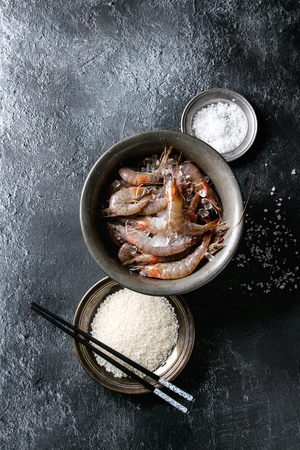 Raw whole fresh uncooked prawns shrimps on ice in vintage metal bowl with cooking ingredients above. Sea salt, rice, garlic, chopsticks over black texture background. Top view with space Stock Photo