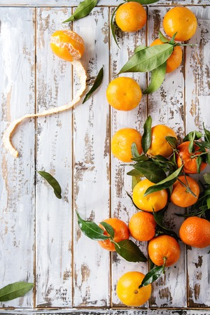 Ripe organic clementines or tangerines with leaves over white wooden plank table as background. Top view, space. Healthy eating Stock Photo