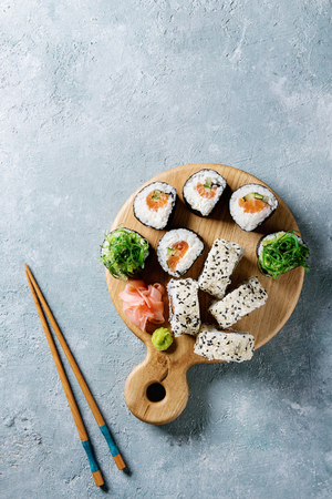 Homemade sushi rolls set with salmon, sesame seeds serving on wood serving board with pink pickled ginger, soy sauce, wasabi, seaweed salad, chopsticks on gray texture background. Top view, space