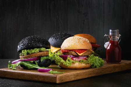 Set of homemade burgers in black and white buns with avocado, tomato sauce, lettuce, arugula, cheese, onion on wood serving board over dark table. Rustic style. Homemade fast food.