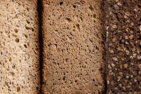 Variety loaves of sliced homemade rye bread whole grain and seeds. Top view, close up. Healthy eating food background