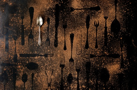 Vintage tablespoon and shapes of disappeared cutlery under brown dust over black metal background. Top view