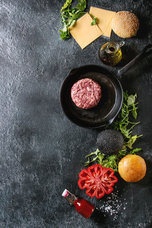 Ingredients for cooking hamburger. Meat beef burger in pan, cheese, ketchup sauce, tomato, black and white buns, arugula salad over dark texture background. Top view with space. Homemade fast food Stock Photo