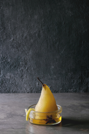 Traditional dessert poached pear in white wine served in glass bowl with syrup and lemon zest over gray texture table. Banque d'images