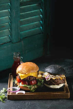 Homemade black and white buns hamburgers with beef, mozzarella cheese, sprouts, arugula, served on wooden slate serving board with french fries and ketchup sauce on dark table. Light via old jalousie