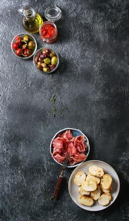 Ingrédients pour faire des tapas ou bruschetta. Pain croustillant, prosciutto au jambon, tomates séchées au soleil, huile d'olive, olives, poivre, légumes verts sur assiettes sur fond de texture sombre. Vue de dessus avec espace Banque d'images - 91861488