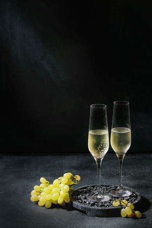 Two glasses of white champagne served on black wooden decorative board with green grapes over dark texture background. Copy space Foto de archivo
