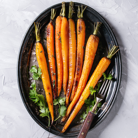 Roasted young whole carrot with greens and sea salt. Served on vintage metal tray with cutlery over gray concrete texture background. Top view with space. Square image